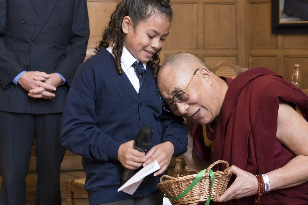 His Holiness the Dalai Lama Receiving a Gift from Local School Children. Photograph by Keiko Ikeuchi.